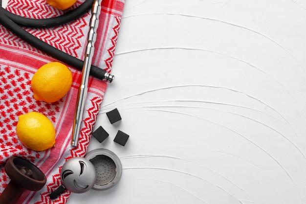 Partes de narguilé e limões em guardanapo vermelho na vista superior branca