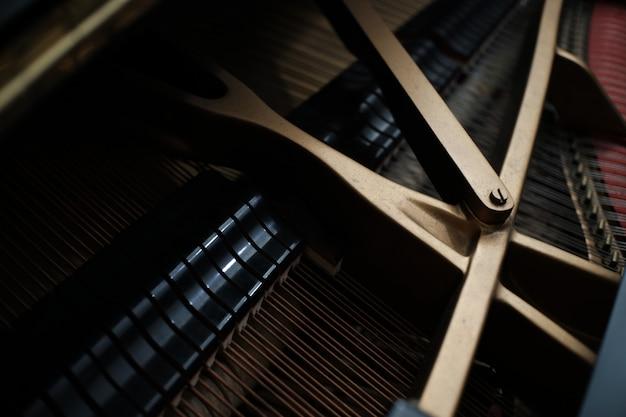 Partes internas de uma corda de piano vertical e uma chave de ajuste nos pinos.