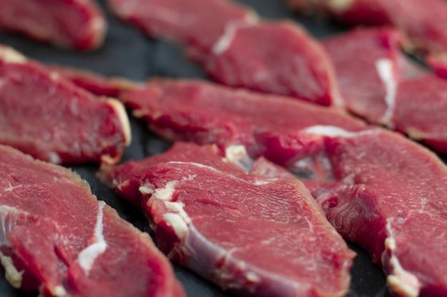 Partes vermelhas de vitela fresca, cortadas em bifes finos crus, dispostas em uma placa de madeira.