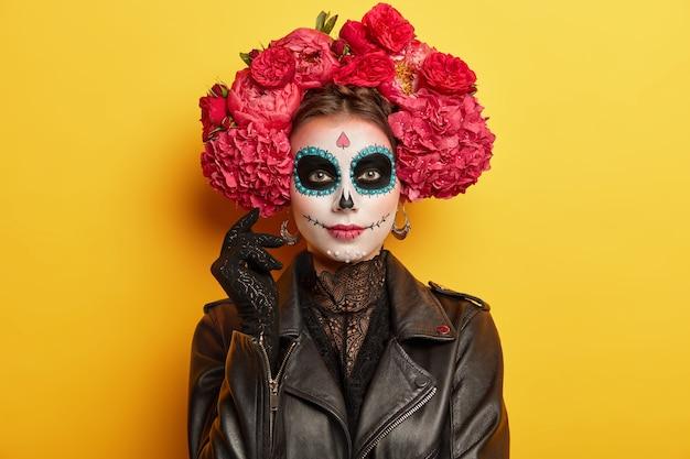 Participante feminina do feriado mexicano tem maquiagem profissional, olhos negros e coroa de peônias vermelhas vestida como modelos espirituais dentro de uma parede vívida