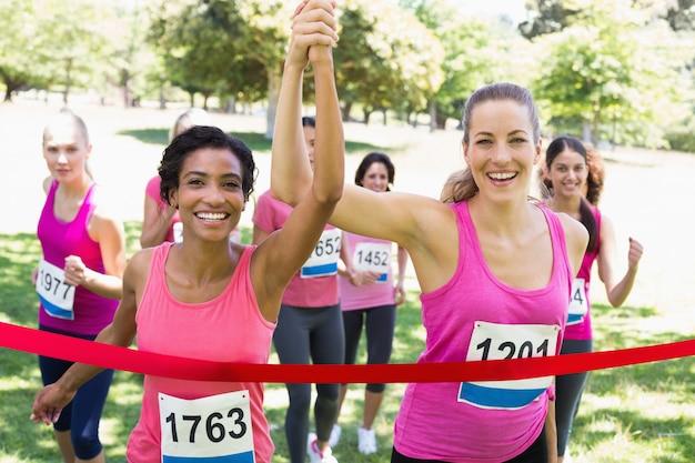 Participantes do câncer de mama cruzando a linha de chegada na corrida