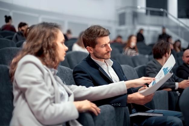 Participantes do seminário de negócios discutem cronogramas financeiros visão traseira