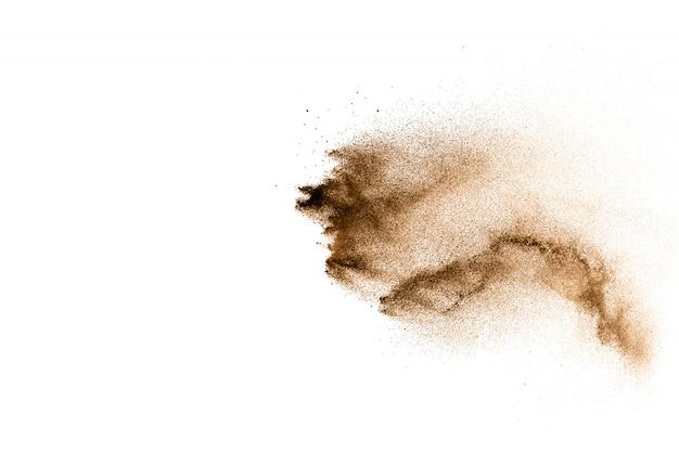 Partículas de brown splattered no fundo branco. respingo de poeira marrom.