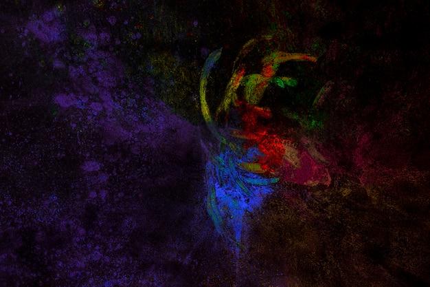 Partículas de cores holi misturadas com a mão no pano de fundo preto