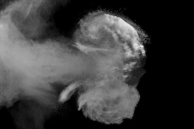 Partículas de poeira branca exalam no ar. pó de movimento estourou em fundo escuro.