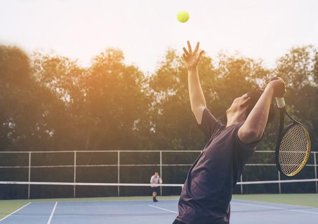 Partida de tênis que um jogador servindo