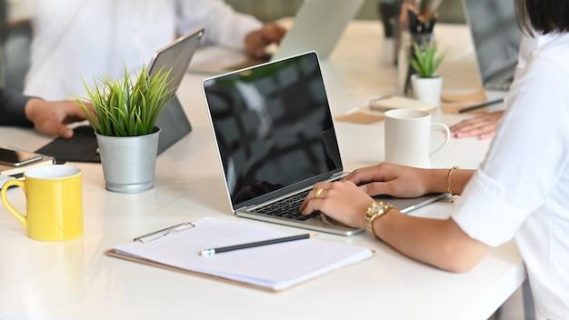 Partida feminina trabalhando em seu projeto com o laptop na sala de reuniões.