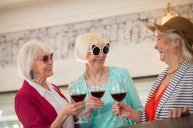 Partido. três senhoras felizes sêniors dando uma festa e parecendo se divertindo enquanto bebem vinho