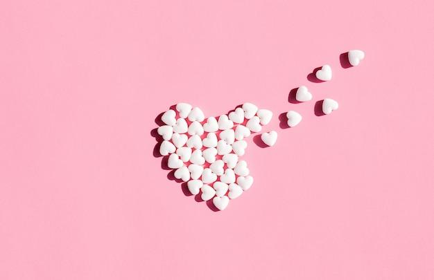 Partindo o coração de comprimidos em forma de coração branco isolados. vitaminas para doenças cardíacas. assistência médica