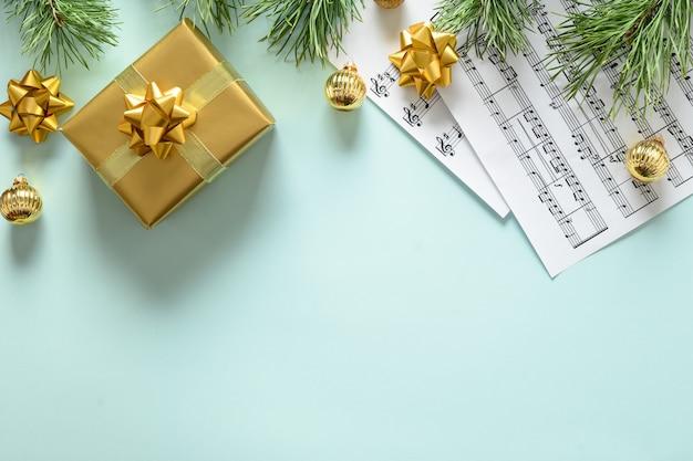 Partituras para canções de natal decoradas com presente dourado e bolas em azul