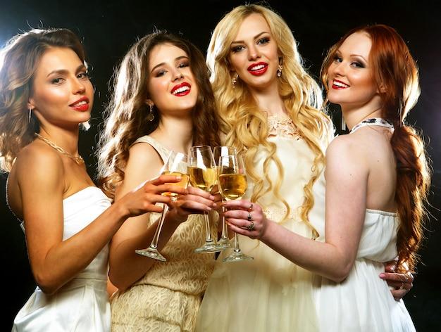Party girls tinindo flautas com vinho espumante