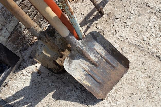 Pás de ferro velhas contra a parede na rua. ferramenta de jardim de trabalho.