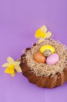 Páscoa ainda vida, bolo de páscoa, frango e ovos de codorna, sobre um fundo violeta.