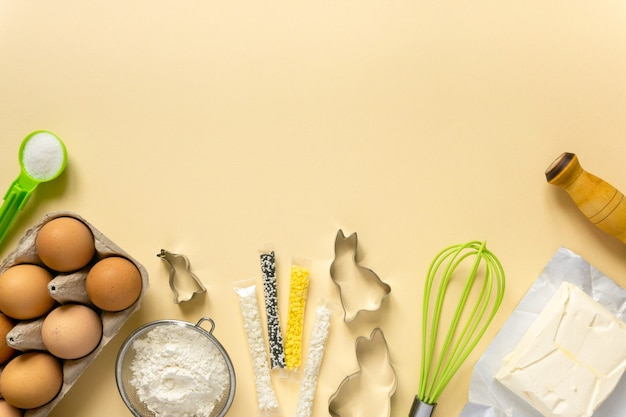 Páscoa assando plana leigos. ingredientes de biscoitos e utensílios de cozinha em fundo bege, espaço para texto.
