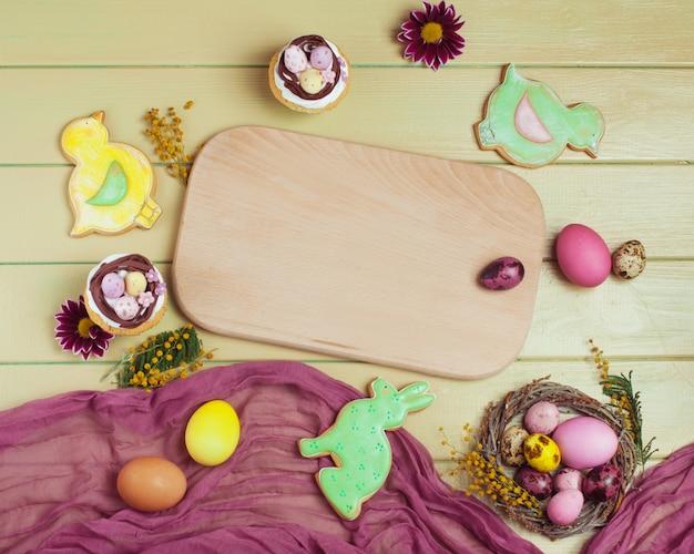 Páscoa cupcakes, gingerbreads, ovos pintados ao redor do tabuleiro vazio