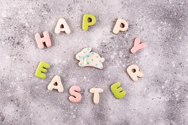 Páscoa feliz colorida que rotula a páscoa feliz do biscoito dos biscoitos e das cookies do gengibre no fundo de pedra.