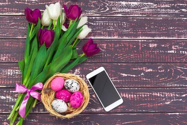 Páscoa, feriados, conceito da tradição e do objeto - próximo acima de ovos da páscoa coloridos, flores da tulipa e smartphone no fundo de madeira