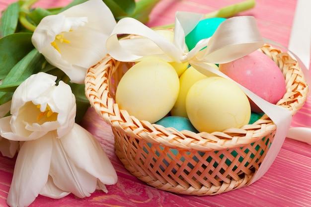 Páscoa, feriados, tradição e objeto close-up de ovos coloridos e flores tulipa sobre tábuas de madeira