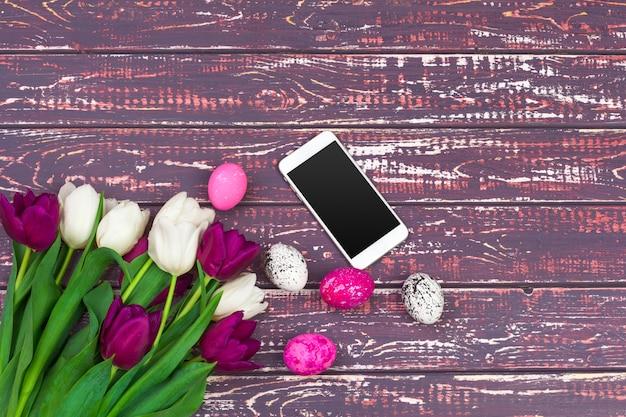 Páscoa, feriados, tradição e objeto, close-up de ovos de páscoa coloridos, flores tulipa e smartphone