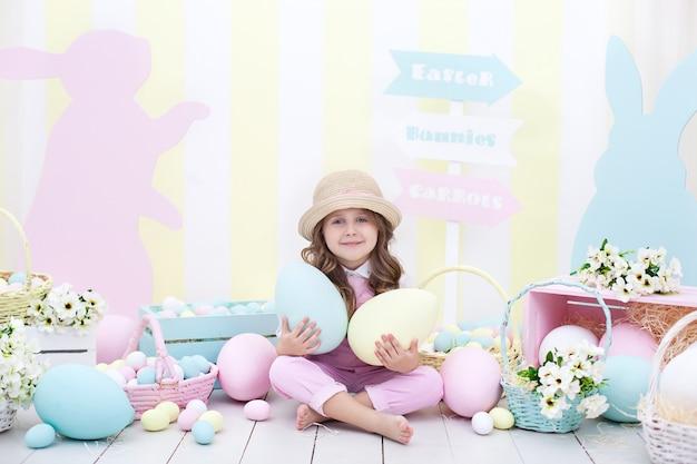Páscoa! garota detém grandes ovos multicoloridos em suas mãos no interior da páscoa. um bebê fofo está perseguindo ovos de páscoa. decoração de páscoa criança e jardim. fazendeiro. colheita