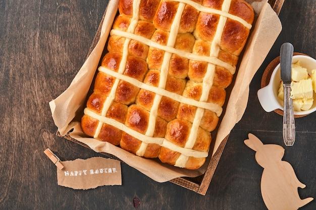 Páscoa hot cross buns. café da manhã tradicional e decorações do feriado de cozimento de páscoa rabbiton fundo escuro de madeira velho. cores brilhantes, vista de cima, na mesa de madeira.