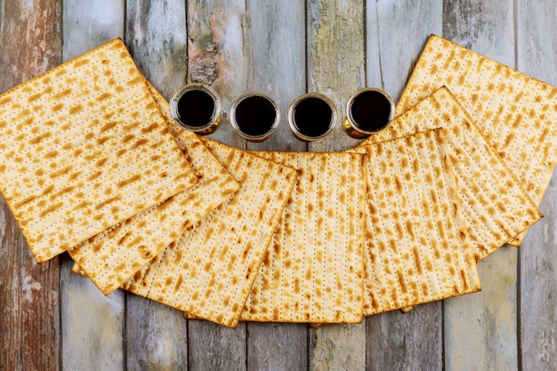 Páscoa judaica pão matzoh feriado, quatro copos de vinho kosher sobre a mesa de madeira.