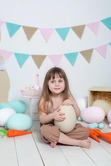 Páscoa! menina de macacão senta-se com um ovo de páscoa grande. localização de páscoa, decorações. férias em família, tradições. quarto colorido. desenvolvimento infantil. decoração de páscoa. a criança brinca no berçário