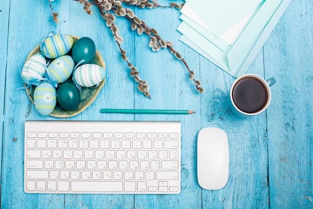 Páscoa no local de trabalho de escritório, mesa de madeira azul. teclado de computador e uma xícara de café