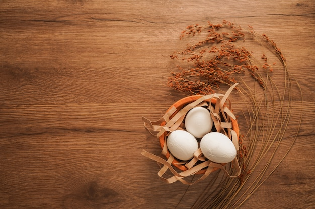 Páscoa, ovos brancos em papel pardo e planta seca na mesa de madeira