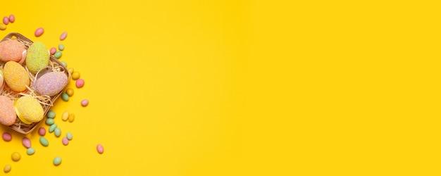 Páscoa. ovos coloridos em uma cesta de vime com decorações coloridas em um fundo amarelo