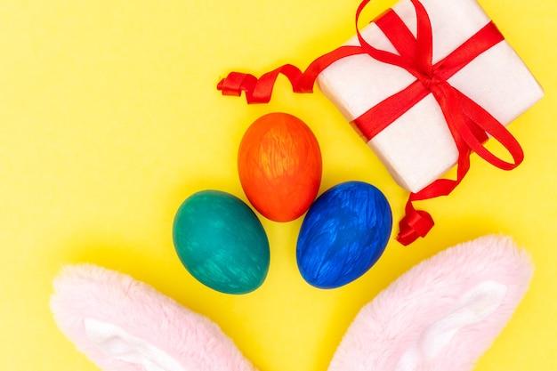 Páscoa plana coloca ovos coloridos pintados, caixa de presente branca com fita vermelha, orelhas de coelho rosa em fundo amarelo brilhante