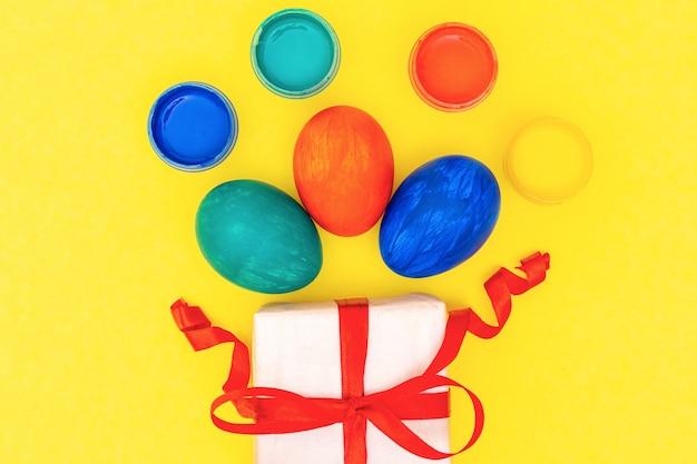 Páscoa plana coloca ovos pintados multicoloridos, tintas e caixa de presente branca com fita vermelha em fundo amarelo brilhante.