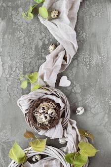 Páscoa plana deitada em fundo escuro. ovos de codorna no ninho de pássaro, têxteis de linho, folhas frescas e coroa de vime na mesa escura. decorações de páscoa de plástico grátis.