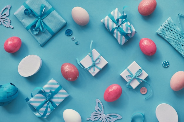 Páscoa plana leigos em branco e rosa na superfície de papel azul hortelã com ovos e presentes