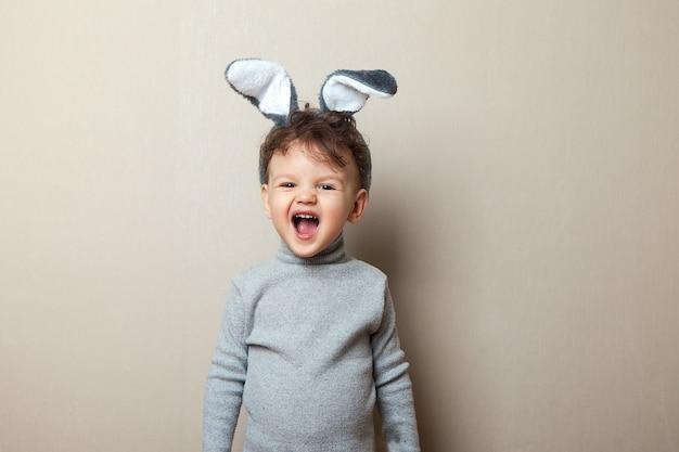 Páscoa. um menino com orelhas de coelho gritando em roupas cinza
