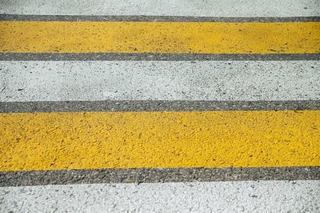 Passadeira na rua da cidade, listras amarelas e brancas no asfalto cinza.
