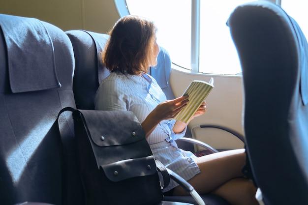 Passageira adulta sentada na poltrona perto da janela na cabine da balsa. mulher, levando uma revista de leitura de viagem por mar, livro. transporte marítimo, viagens, turismo