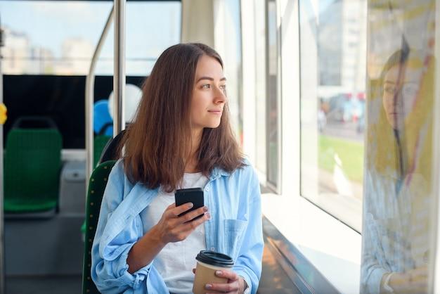 Passageira bonita senta-se com smartp aprimorar enquanto se move no moderno bonde ou metrô. viagem no transporte público.