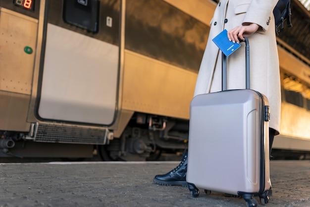 Passageira com mala e passaporte na estação ferroviária.