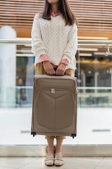 Passageira irreconhecível segurando mala, posando no terminal do aeroporto internacional duty free