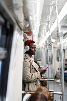Passageiro afro-americano no metrô, usando um smartphone móvel, ouve música com fones de ouvido