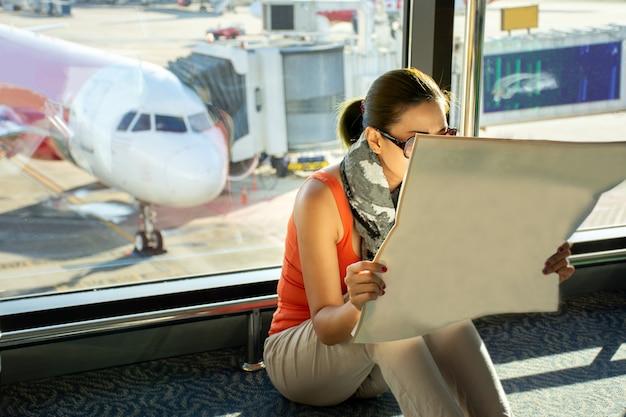 Passageiro asiático para ler as informações enquanto aguarda a viagem no terminal