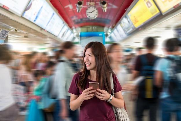 Passageiro da mulher asiática com roupa casual usando o telefone móvel inteligente na interexchange entre sta