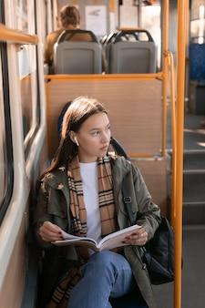 Passageiro de cima segurando um livro e olhando para longe
