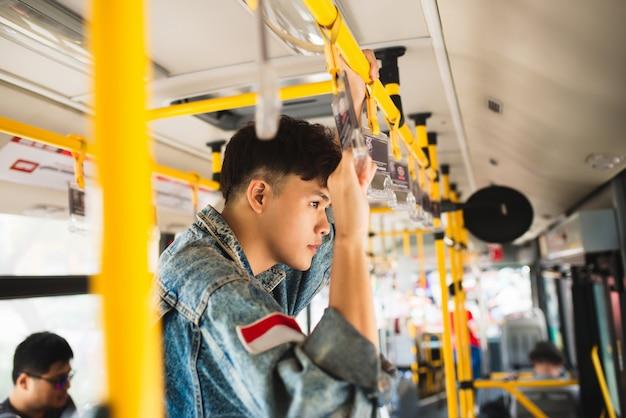 Passageiro de homem asiático com terno casual, de pé dentro do ônibus.