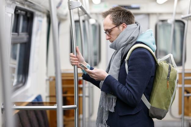 Passageiro de homem de óculos com mochila segurando o corrimão, usando e olhando para o telefone móvel esperto no trem subterrâneo