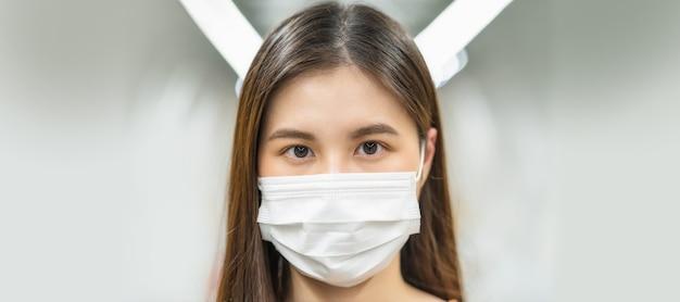 Passageiro de jovem mulher asiática usando máscara cirúrgica e olhando para a câmera no trem do metrô