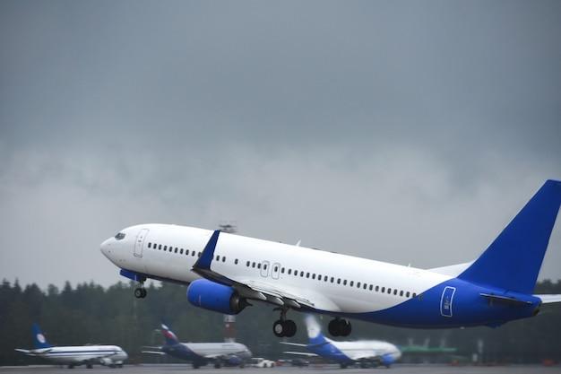 Passageiro decola para o céu da pista do aeroporto em tempo nublado com chuva