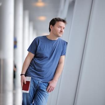 Passageiro do sexo masculino no aeroporto. homem de negócios da idade média que guarda o passaporte e a passagem de embarque.
