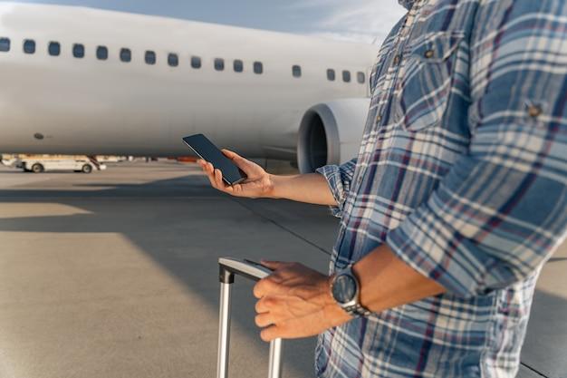 Passageiro do sexo masculino segurando um smartphone e um pente antes do voo